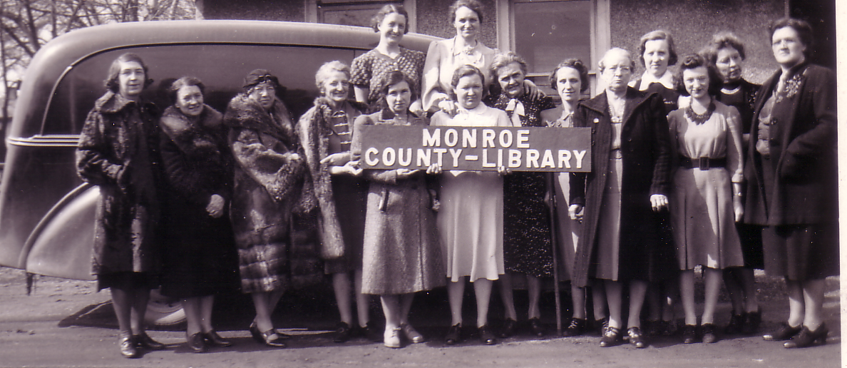 MCLS employees holding sign for Monroe County Library