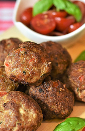 meatballs with a bowl of tomatoes