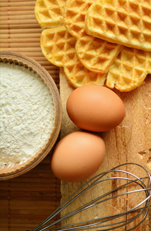 Flour, eggs, waffles, and a whisk