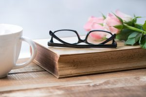 Reading glasses on book with rose